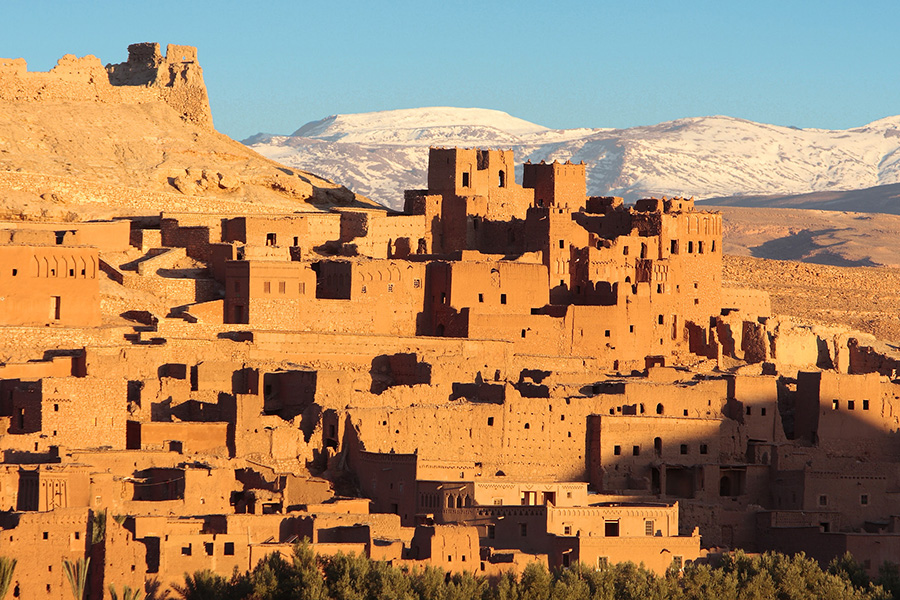 A low sun illuminates Kasbah of Ait Benhaddou in Morocco, with snow-covered mountains in the background December 2007